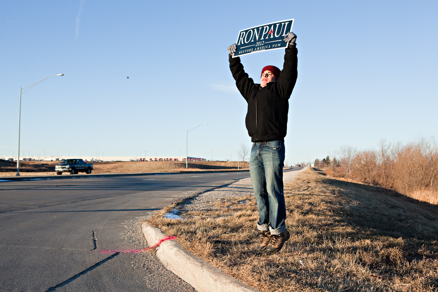A Ron Paul supporter jumps up and down to keep warm and attract attendees to a campaign event in Cedar Falls, Iowa on January 2, 2012.