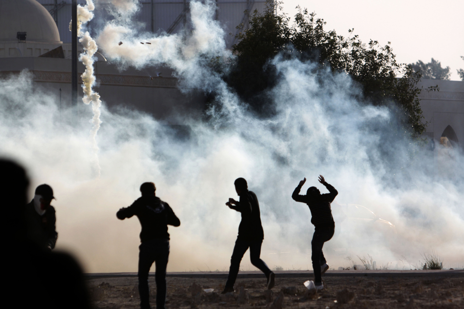 January 21, 2012. Mourners react to tear gas fired by riot police in the Muharraq, Bahrain, cemetery during the politically charged funeral of Yousif Mowali, 24. Authorities say Mowali drowned. His family and opposition human rights activists say relatives searching for him had been told by police he was in custody and that his body showed burns and bruises consistent with torture.