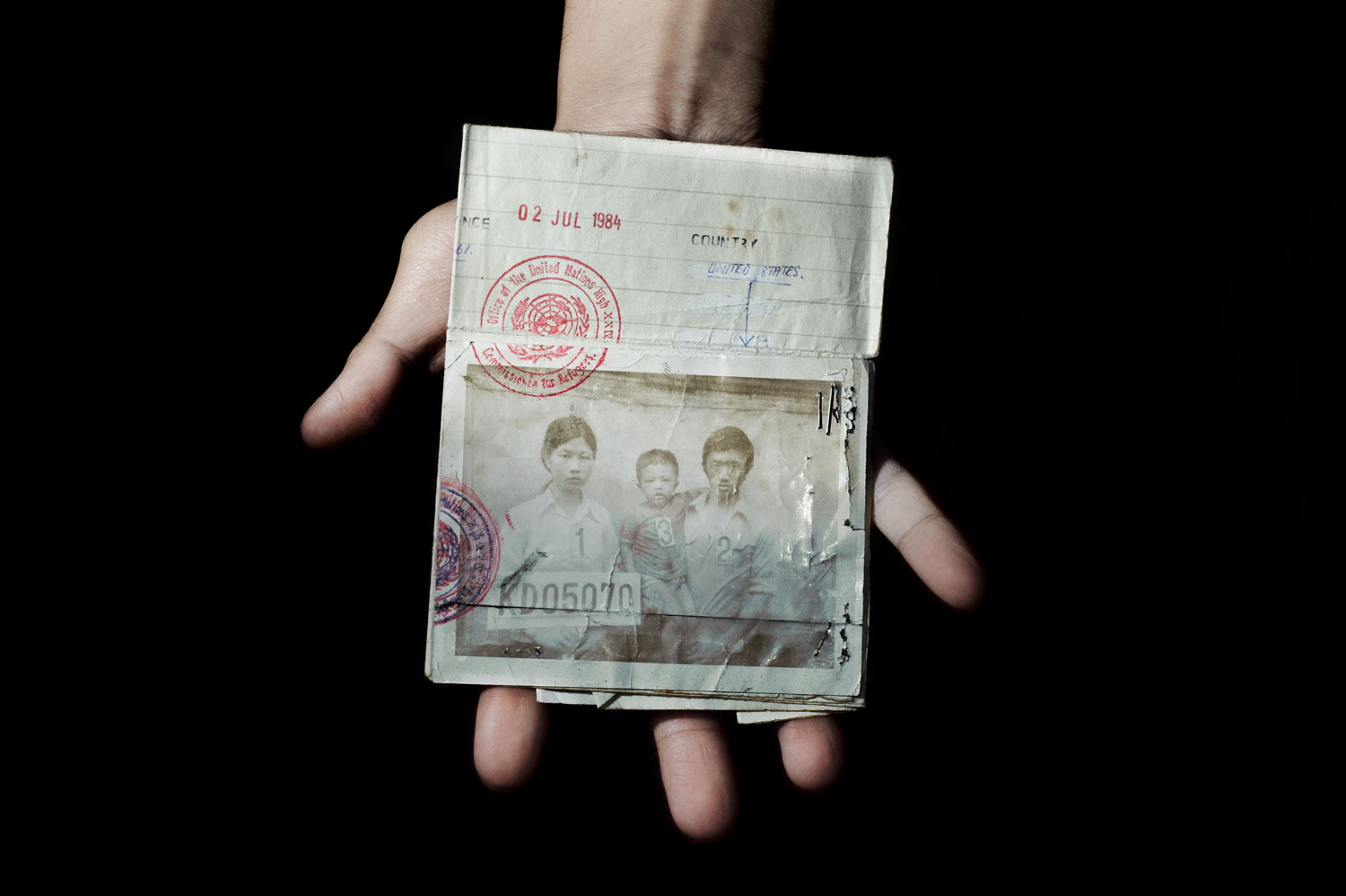Bronx, New York City, September 2011. Sonny Vaahn, 25, holds the refugee identification card of his family members, which was given upon initial entry into a refugee camp along the Thai-Cambodian border following the end of the Killing Fields in Cambodia.