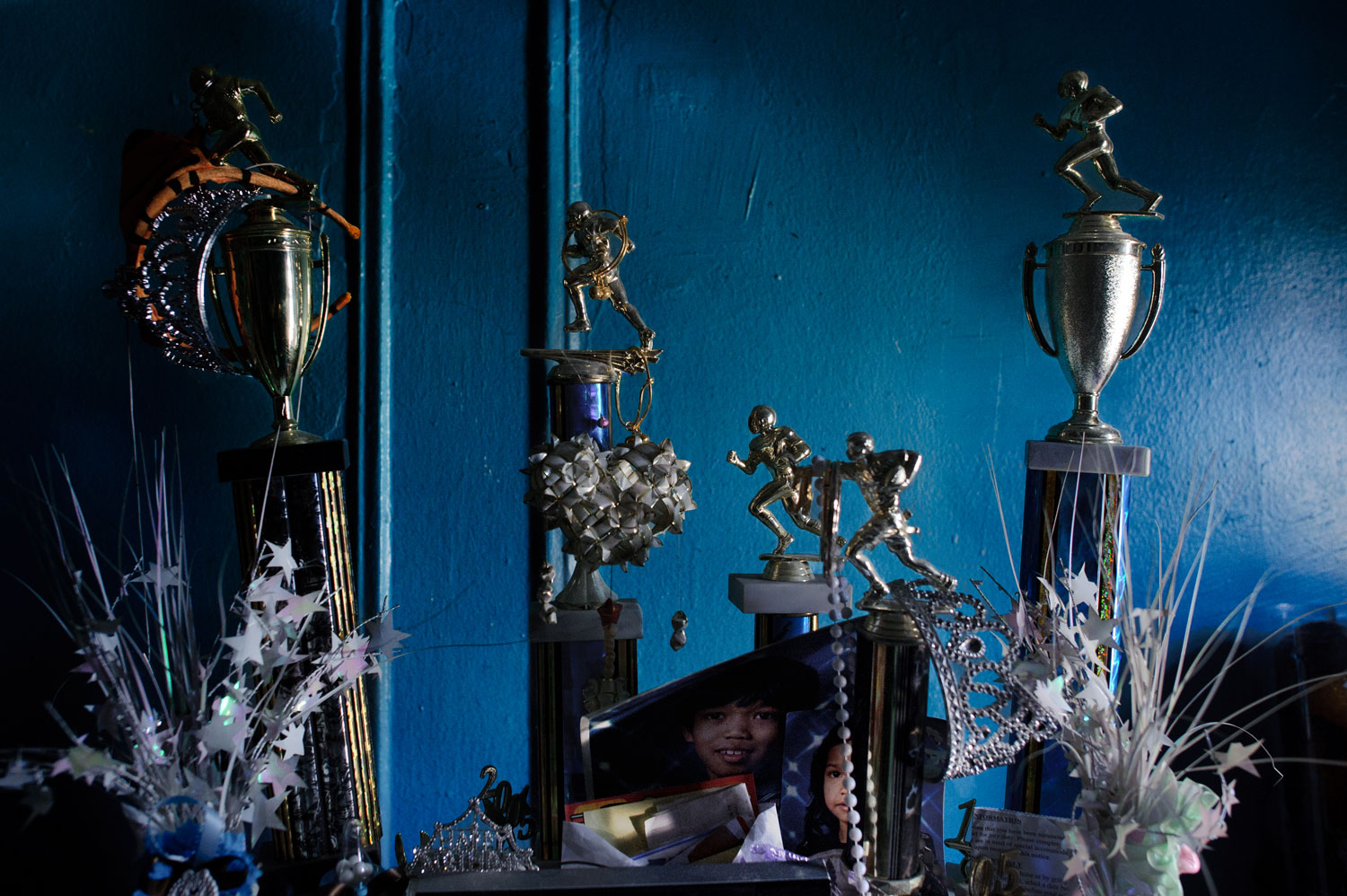 """Bronx, New York City, September 2011.Football trophies accumulated by Sovann Ith, 23. The Bronx is a multiracial community; Cambodian youth in the Fordham area play league football for """"racial respect"""" in the neighborhood."""