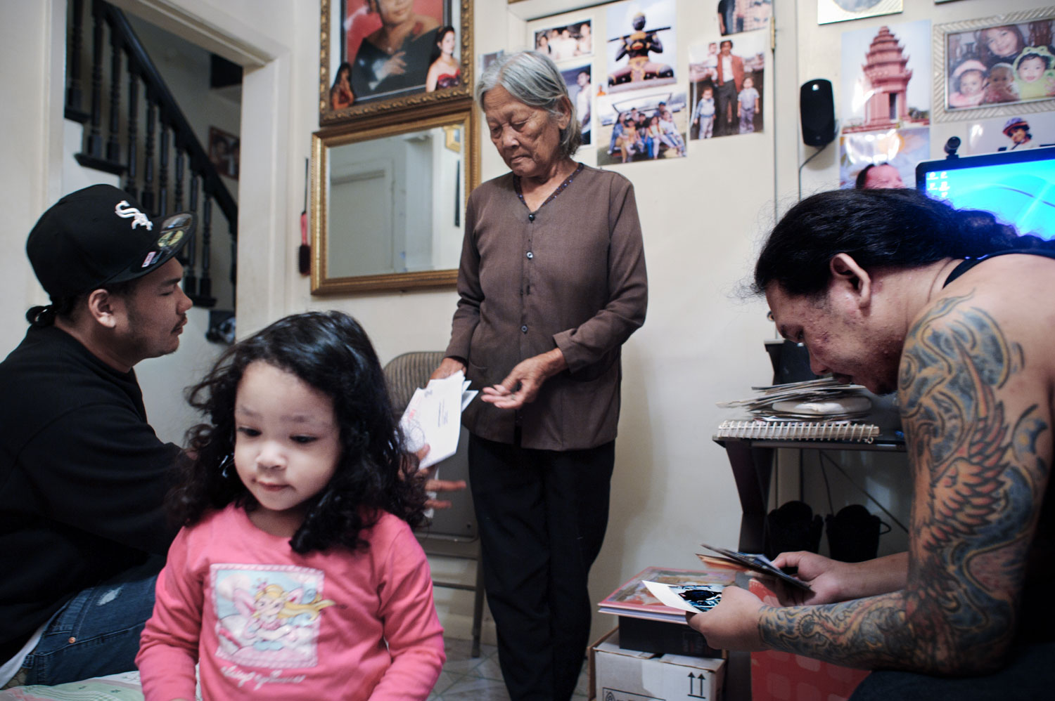Bronx, New York City, September 2011.Three generations of the Duong family look at old family photos and documents from the refugee camps for the first time in the living room of their Bronx apartment. For many families, these documents are their only possessions from Cambodia.