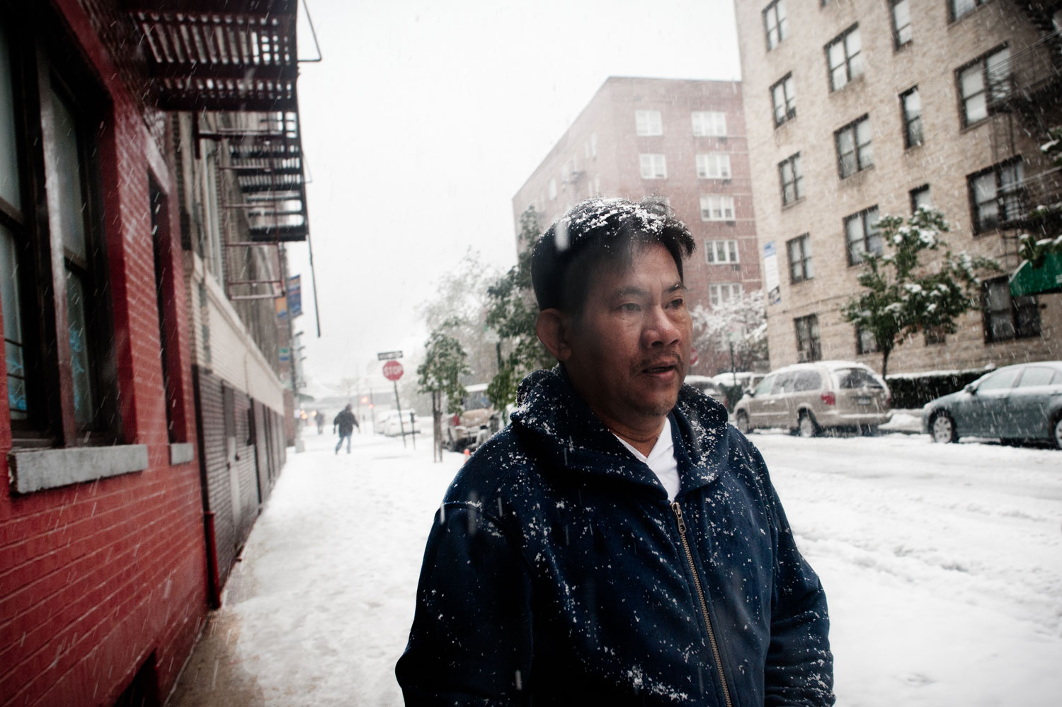 Bronx, New York City, October 2011.Veasna Ngin, 58, walks in front of his Bronx apartment during the first snow of the year. Ngin has lived in the same building with his family since his arrival from a refugee camp in 1981. He assisted in the resettlement of Cambodian orphans as a social worker.