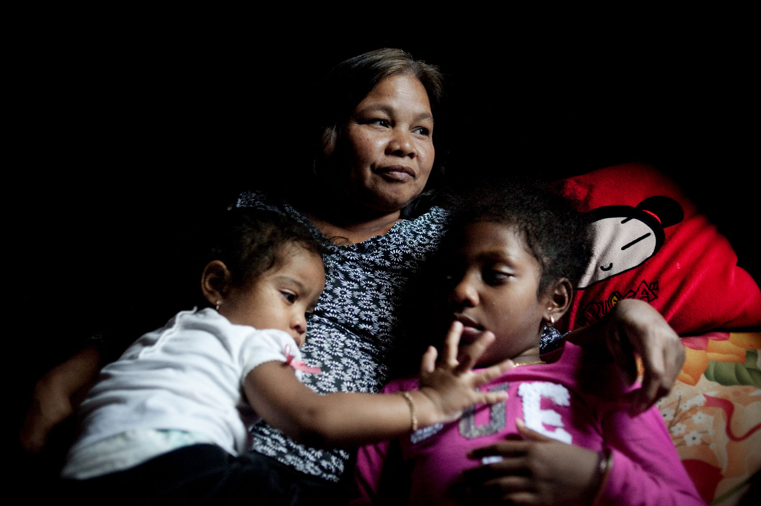 Bronx, New York City, September 2011.Chhan Hui, 59, lies down with her grandchildren, Keinna Lawrence, 2, and Shania Brown, 6, in the living room of their Bronx apartment. Hui immigrated to the States in 1982 and, along with a sister, is the only survivor of her immediate family.