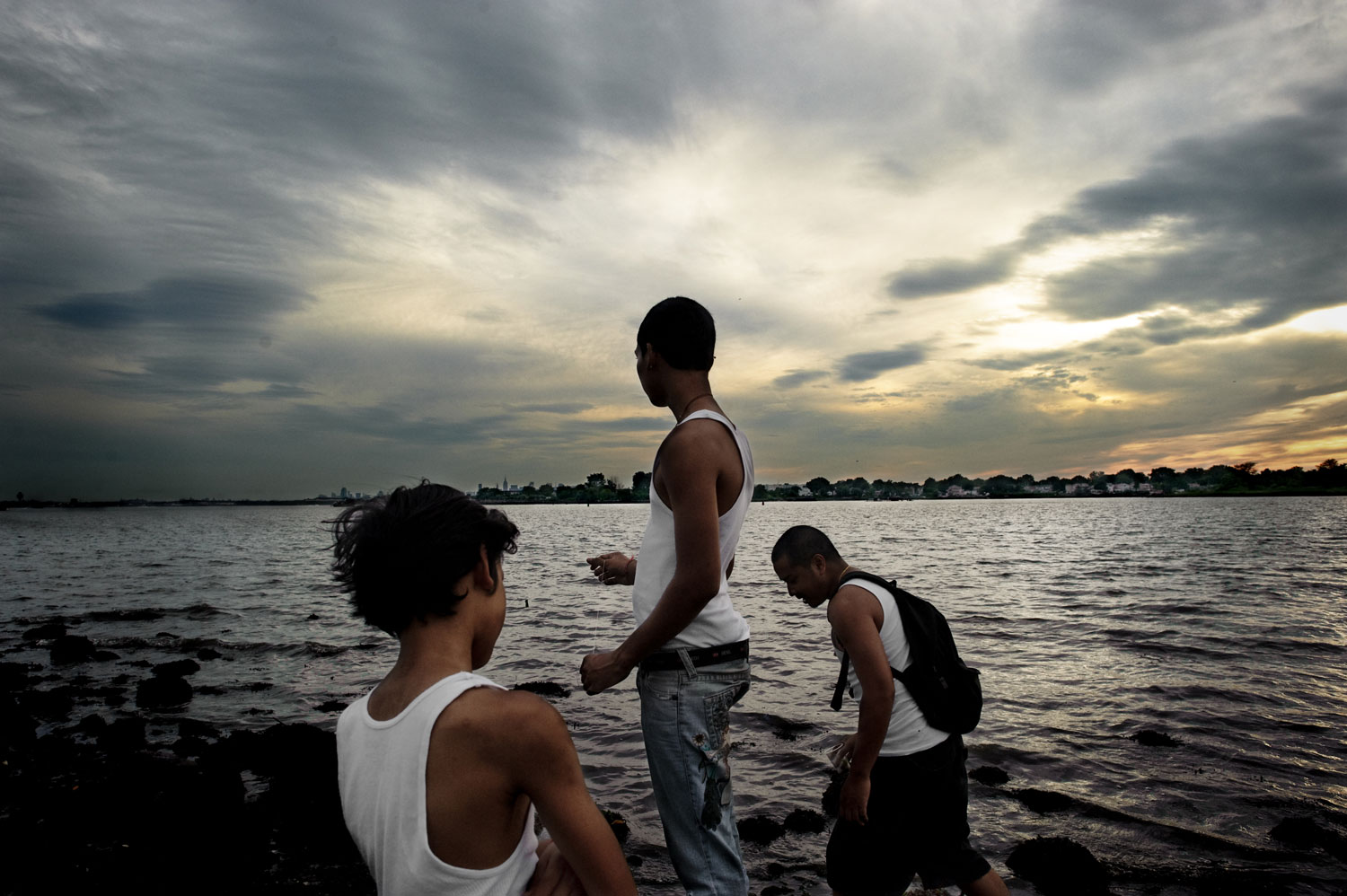 Bronx, New York City, September 2011.From left to right, Joshua Vatthnavong, 11, Joey Vatthanavong, 16, and Sanet Kek, 28, fish without poles at Ferry Point Park in the Bronx.