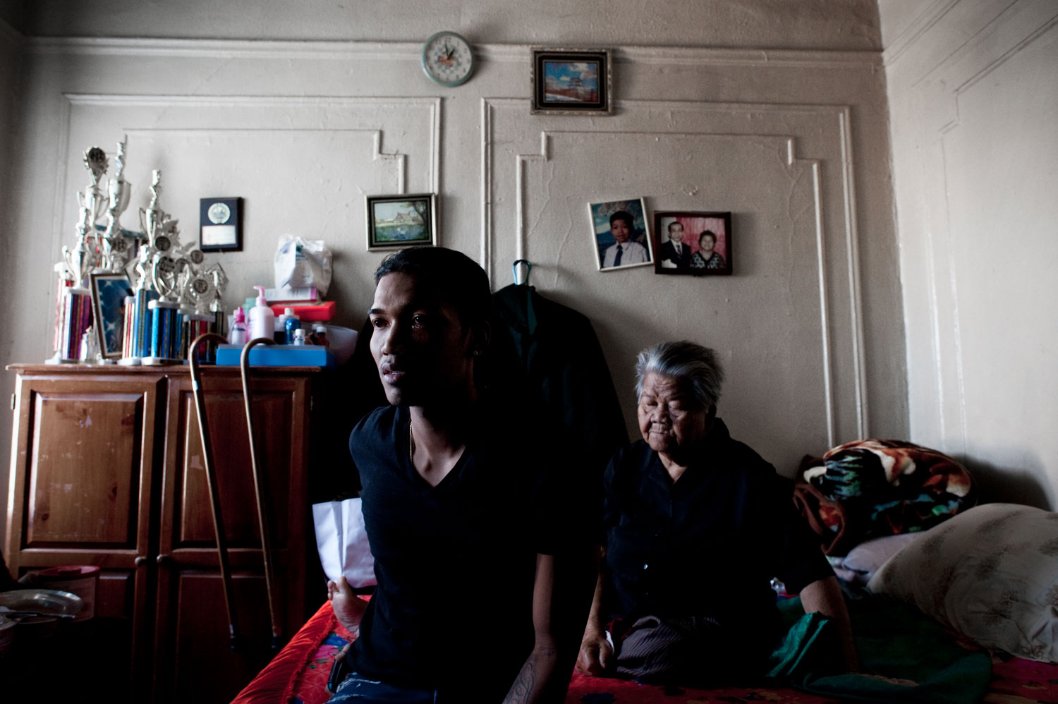 Bronx, New York City, September 2011.Sovann Ith, 23, sits alongside his grandmother, Somaly Ith, 83, in the living room of their Bronx apartment. The complex was once predominantly Cambodian, but is now home to just five families.