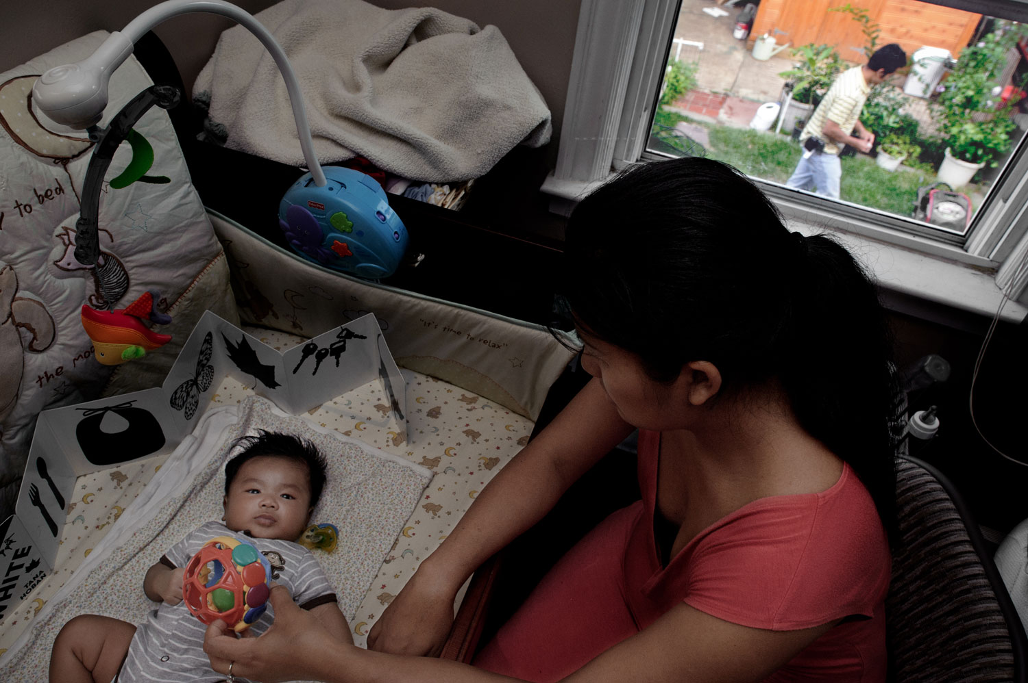 Bronx, New York City, September 2011.Sophie Keo plays with her first-born son while her husband, Paul, works in the yard of their recently purchased home.