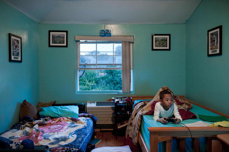 Bronx, New York City, September 2011.Joshua Seyha Tuy, 10, plays video games in his bedroom.