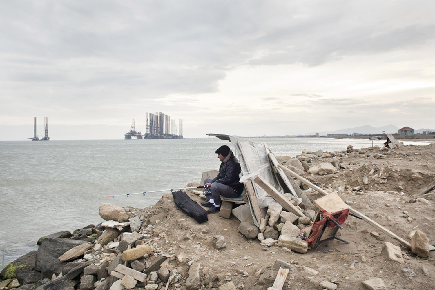 A man fishes at Sahil beach near Baku, Azerbaijan, 2010.