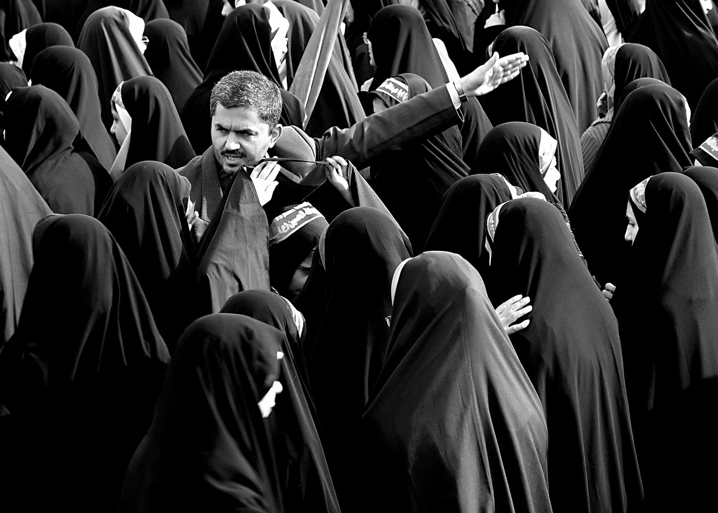 Scholarship winner Pooyan TabatabaeiFebruary 11, 2006. A revolutionary guard tries to rearrange the female crowed at Freedom Square in Tehran during the 26th anniversary of the Islamic Revolution of Iran.