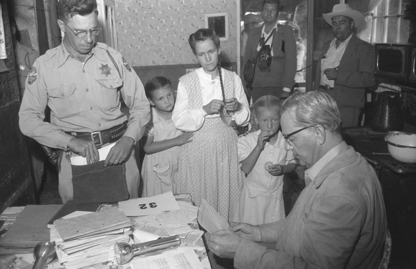 Two girls stand with their mother as she is questioned by an officer and Arizona Attorney General Ross Jones after the 1953 Short Creek raid.