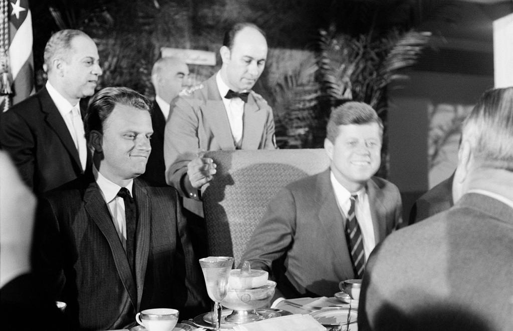 Billy Graham joins newly inaugurated president John F. Kennedy at a national prayer breakfast at Washington's Mayflower Hotel in February 1961.