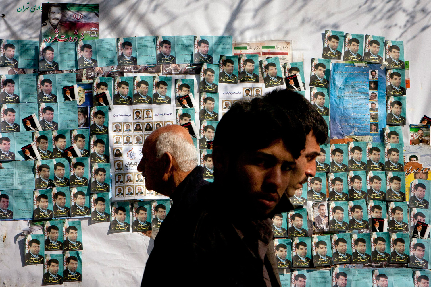 Feb. 28, 2012. Iranians walk past electoral posters for an upcoming parliamentary election on a street in Tehran.
