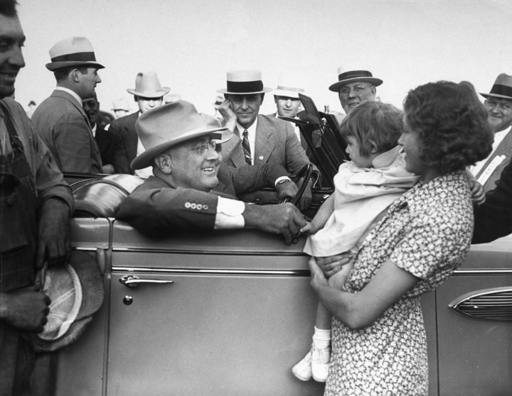President Franklin D. Roosevelt talks to a young mother while sitting in his car during a trip to the West in 1936.