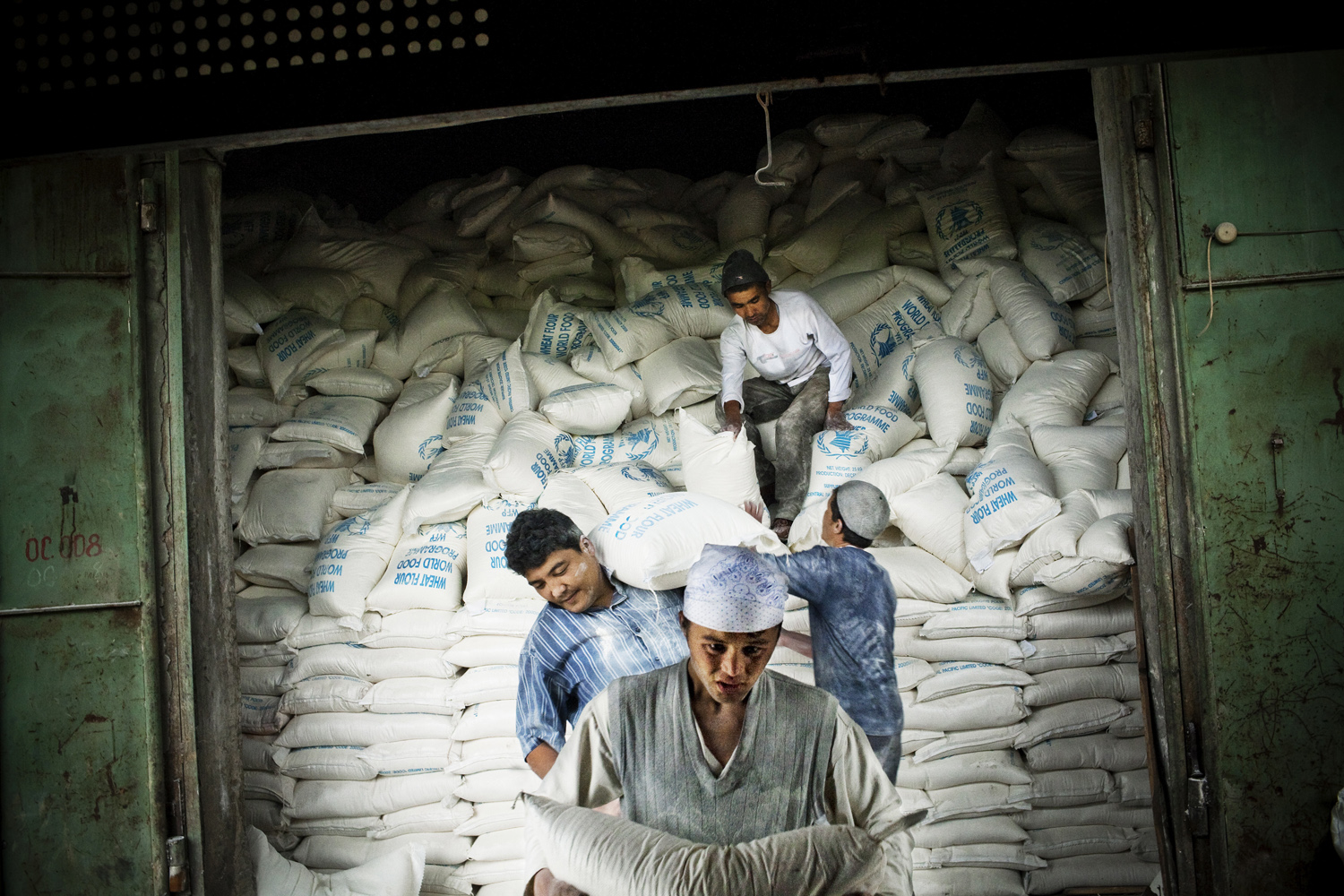 2009. Men unload UN World Food Program sacks of wheat flour in the south of the country.