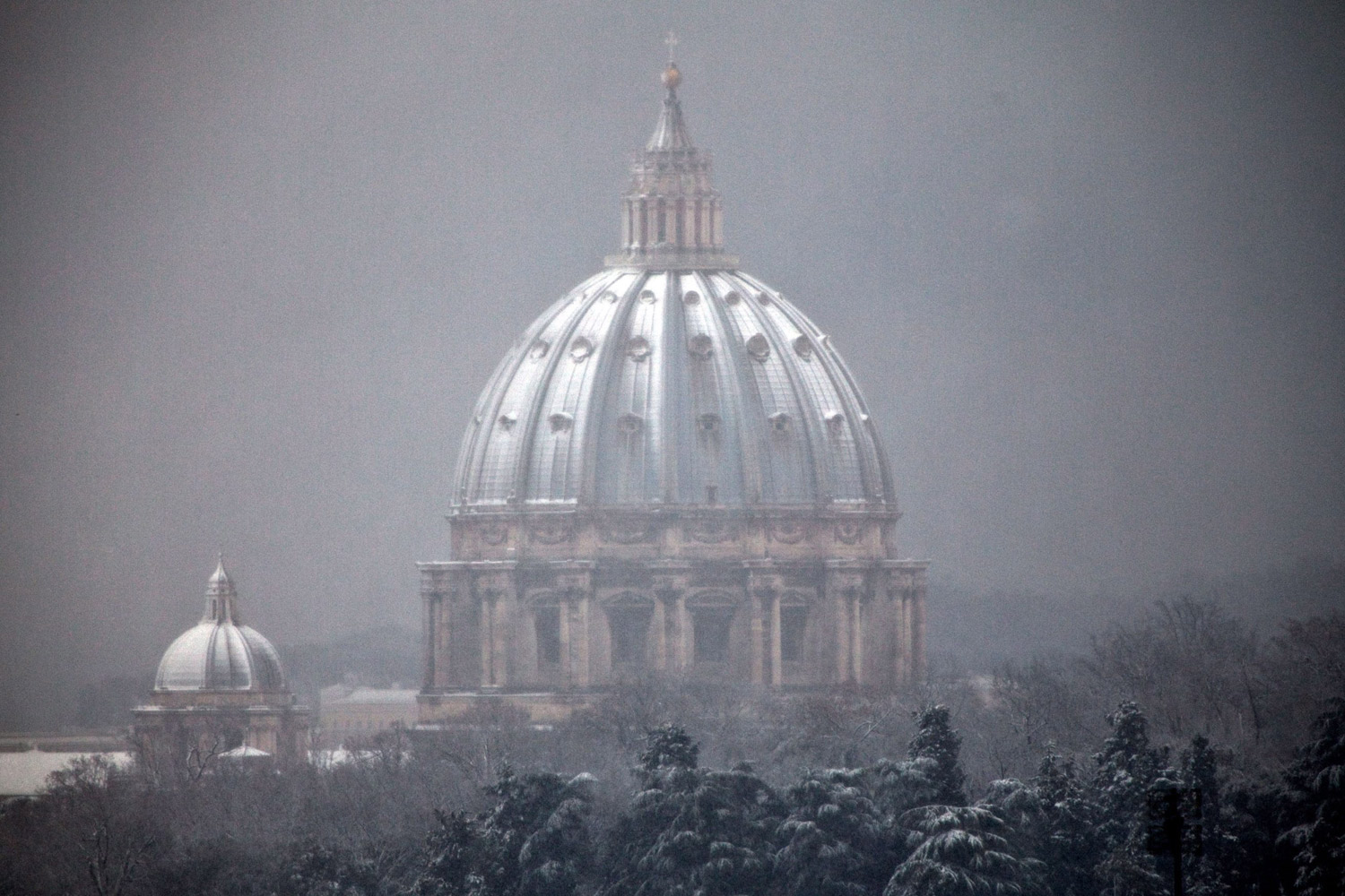 February 3, 2012. The dome of the St. Peter's Basilica in the Vatican is seen through snowfall from a certain distance in Rome.