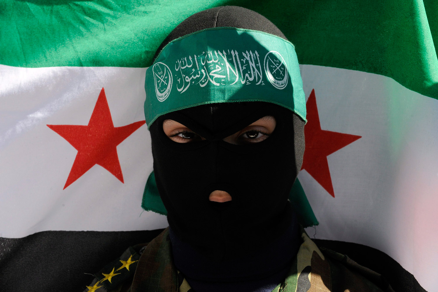 February 5, 2012. A Lebanese anti-Syrian regime protester and supporter of an Islamic group stands in front of a Syrian revolution flag, during a sit-in in front of the Russian Embassy in Beirut.