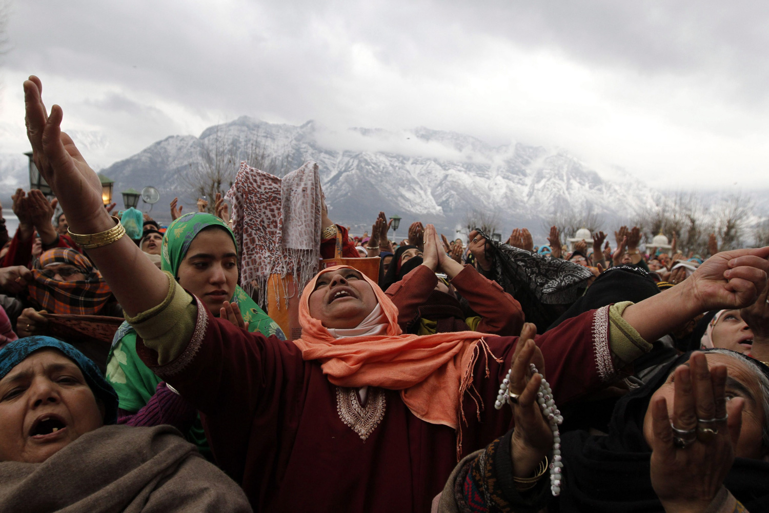 February 5, 2012. Kashmiri Muslim devotees raise their hands for prayers as a head priest displays a relic of Prophet Mohammed at the Hazratbal shrine on the occasion of Eid-e-Milad, or birthday of Prophet Mohammed, in Srinagar, India.
