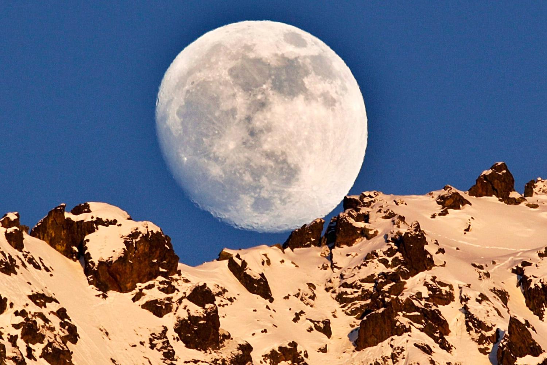 February 5, 2012. The moon rises over the Piz Rosatsch Mountain, as the last rays of the setting sun illuminate the mountain's ridge overlooking Silvaplana,  Switzerland.