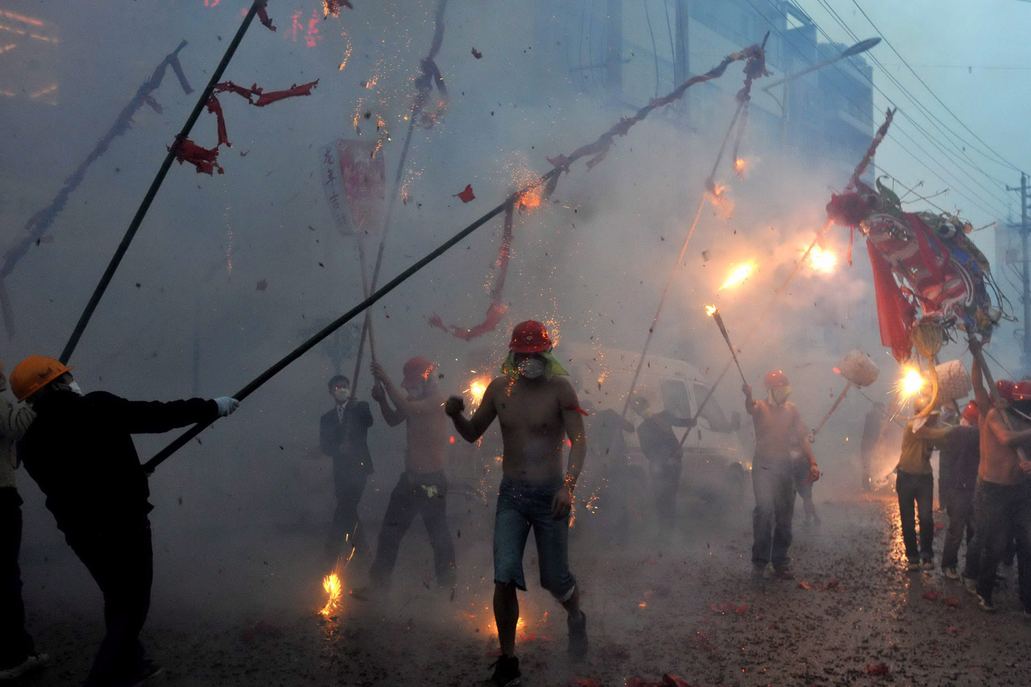 February 6, 2012. Young men parade paper dragons on bamboo sticks as fireworks and firecrackers are thrown at them in a street during the Lantern Festival in southwest Guizhou province, China.