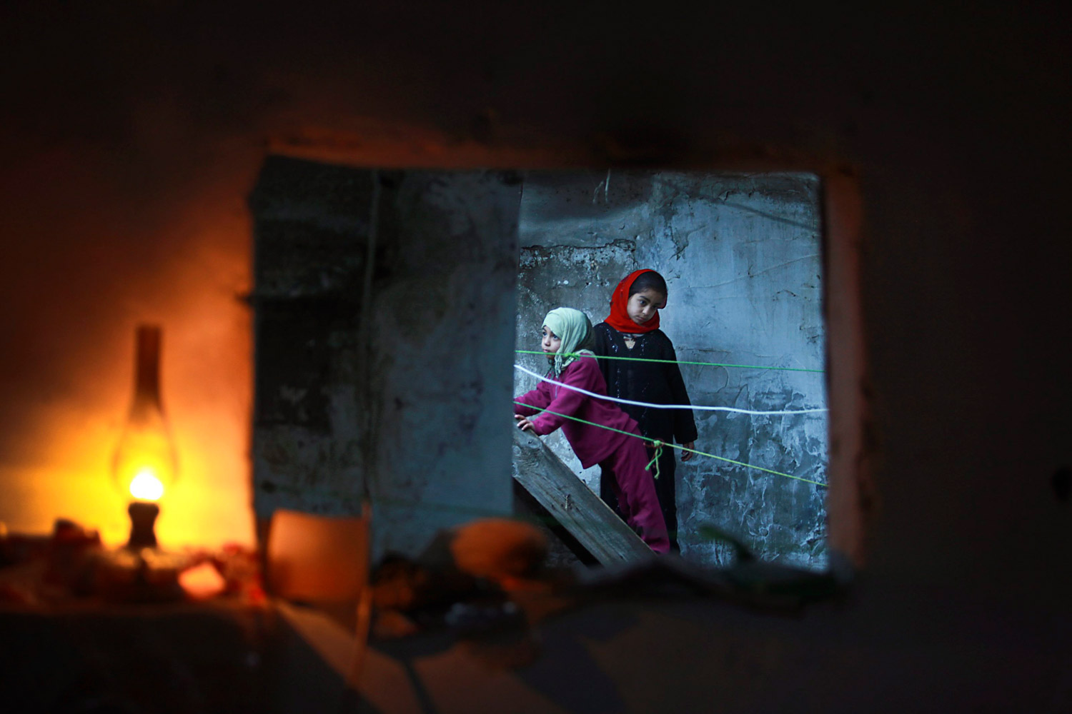 February 7, 2012. Palestinian girls are seen through a window of their familiy's home during an electricity power cut in the Jabaliya refugee camp, Gaza Strip.
