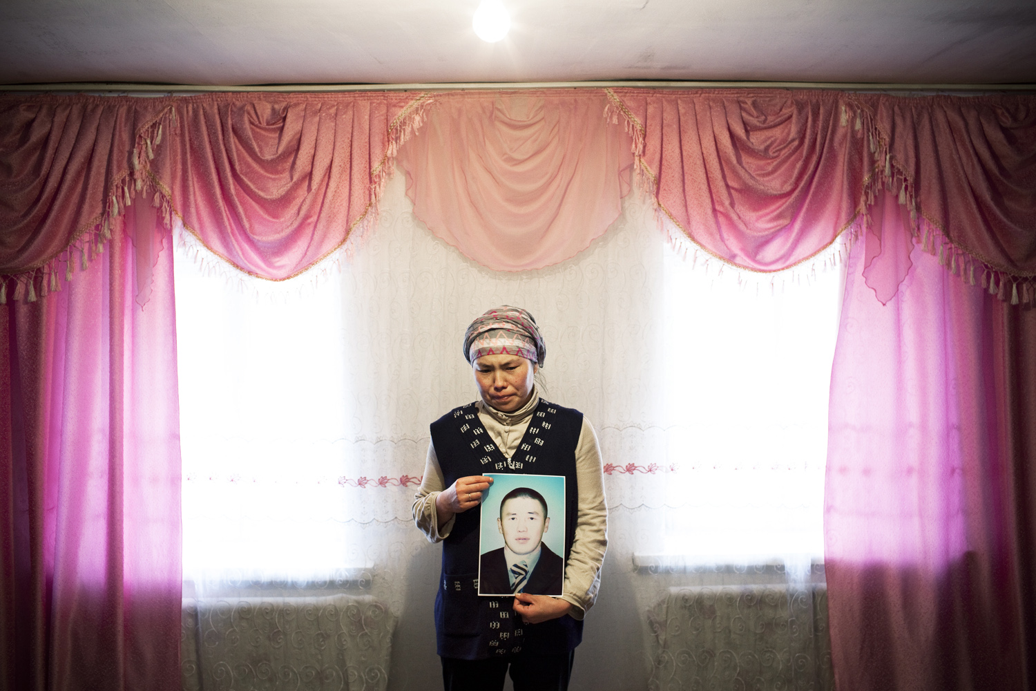 2010. A woman holds a portrait of her husband, a victim of the April 2010 uprising. He was shot and killed by snipers on the roof of the White House, the presidential building in Bishkek, as he attempted to film the uprising.