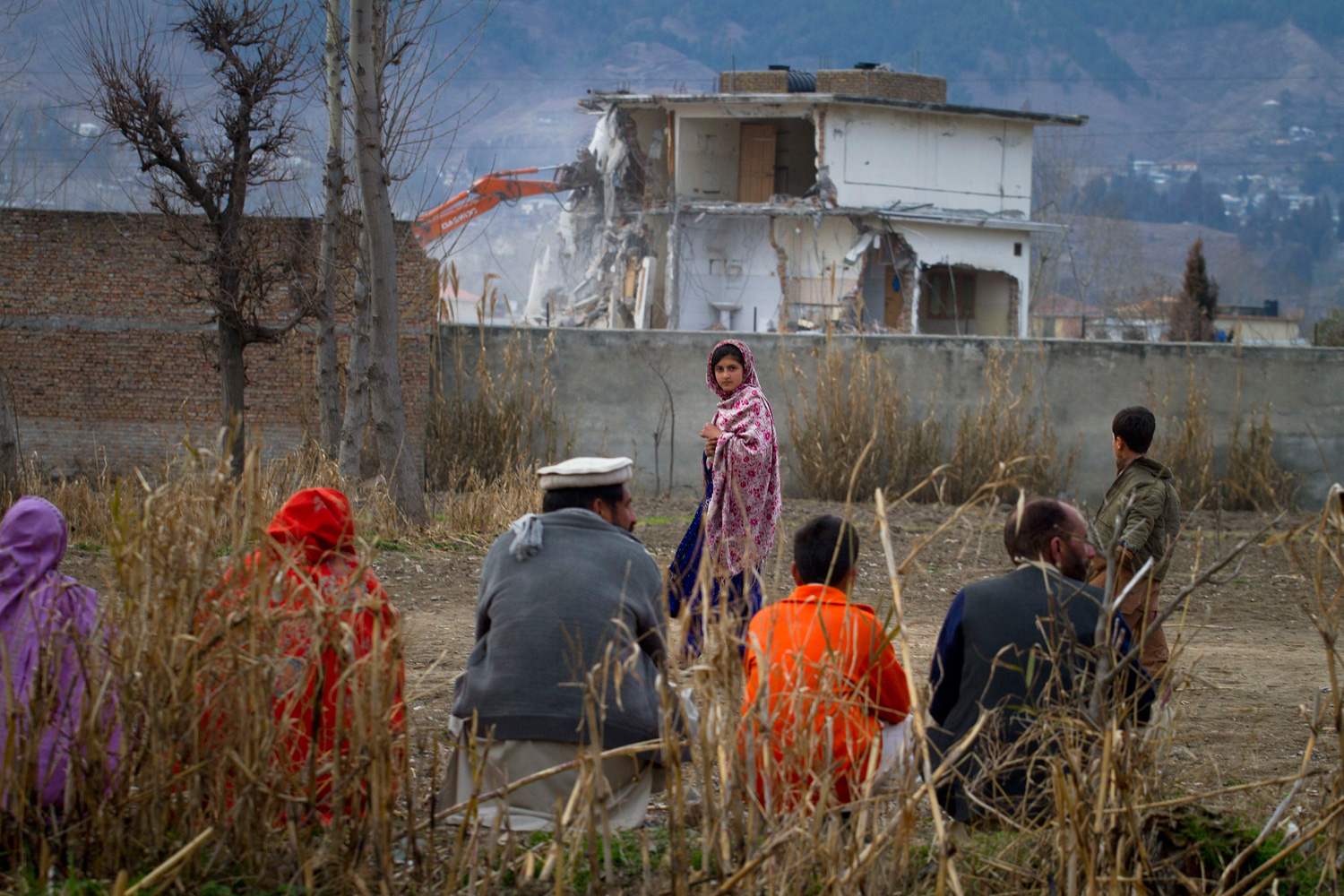 Feb. 26, 2012. A Pakistani family watches the compound of Osama bin Laden being demolished by authorities in Abbottabad, Pakistan.
