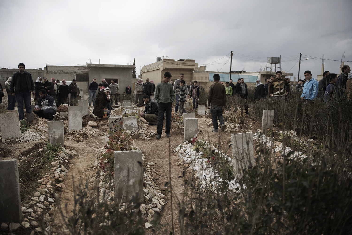 Feb. 28, 2012. Syrians gather at a graveyard during the funeral of a man killed by a shrapnel in the Syrian town of Qusayr.