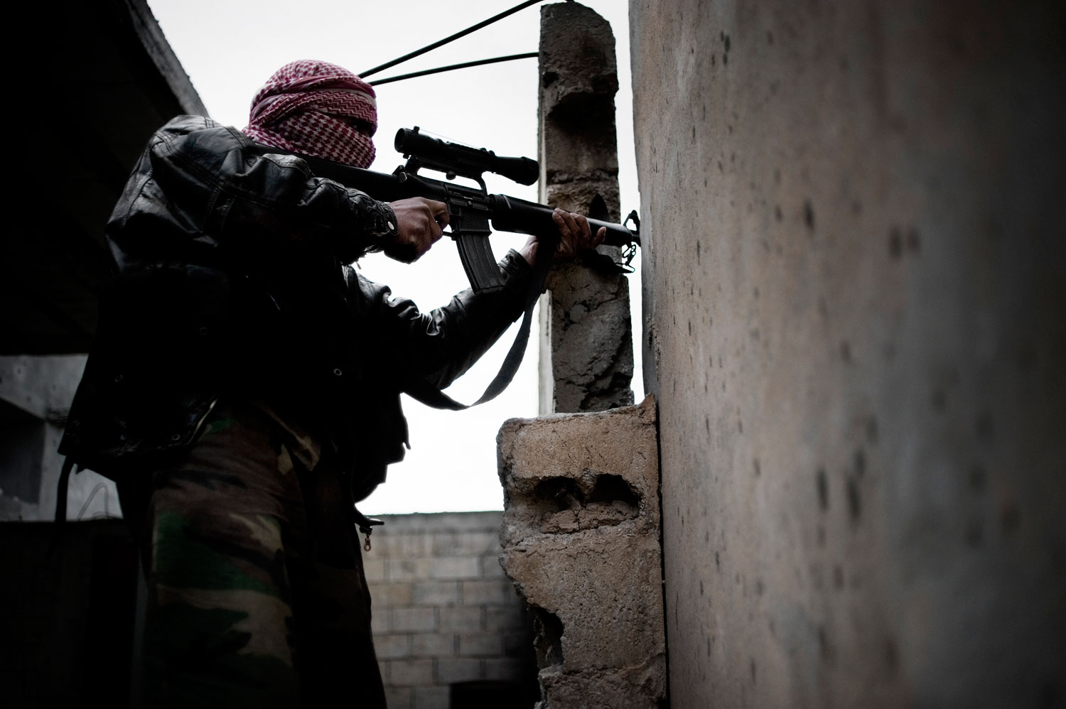 A member of the Free Syrian Army shoots at the Syrian army in Al Qsair. Jan. 24, 2012