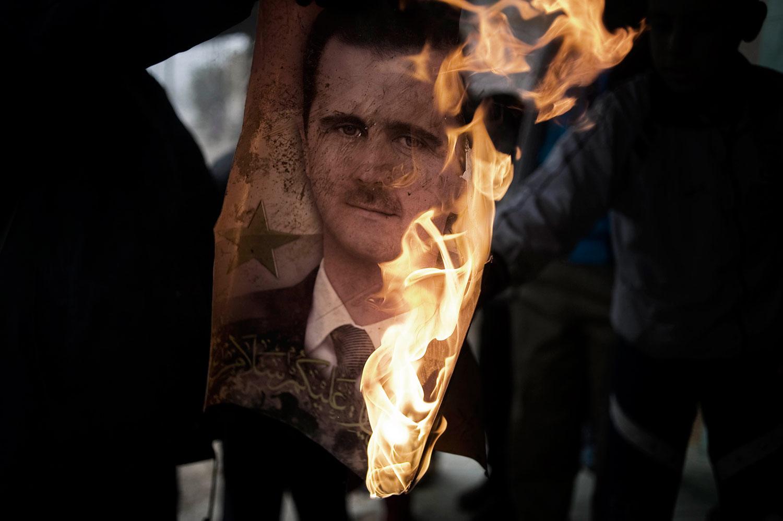 A member of the Free Syrian Army burns a portrait of Bashar Assad in Al Qsair. Jan. 25, 2012