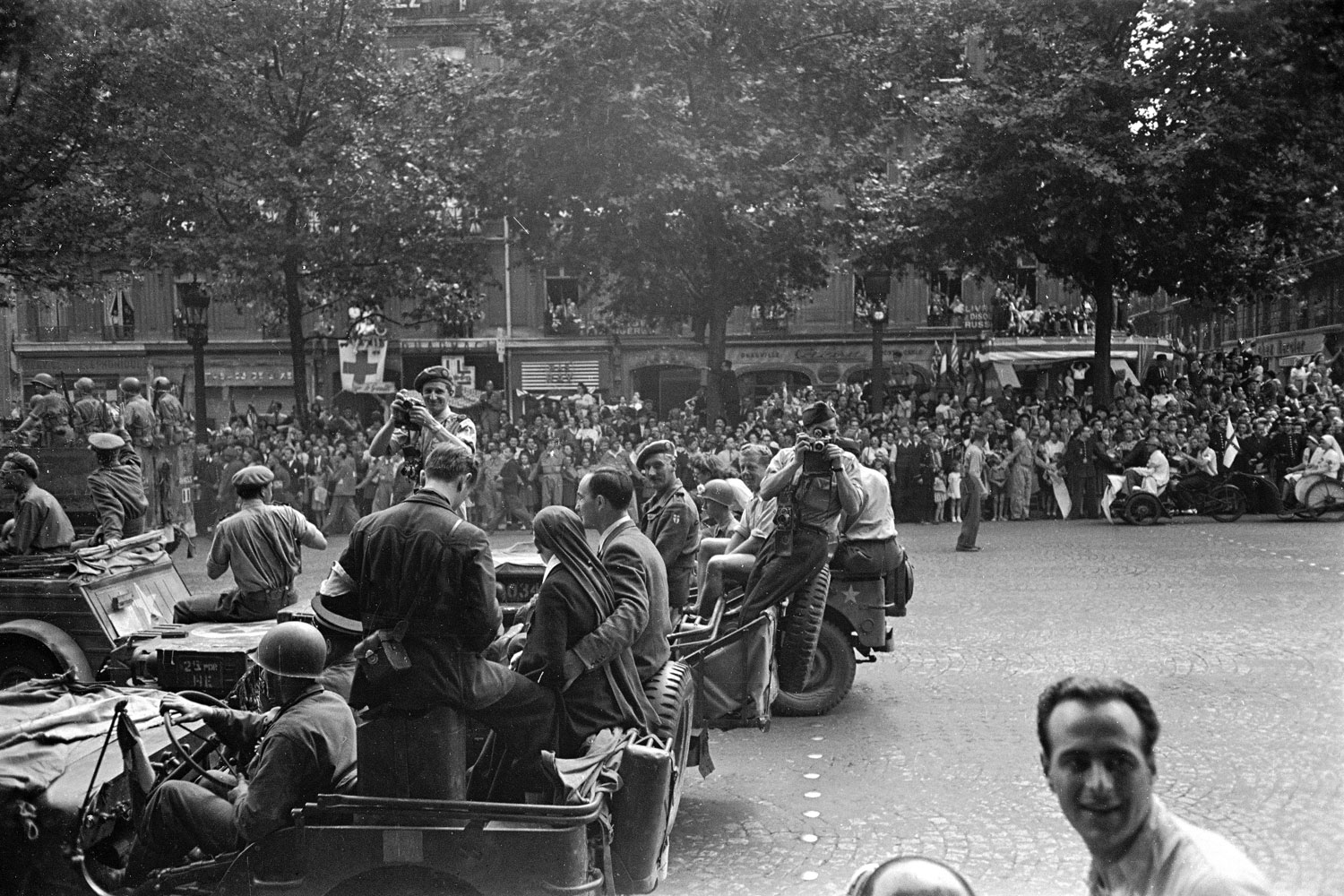 Allied troops and journalists — including photographers Robert Capa (on the back of a Jeep with a camera in front of his face) and George Rodger (with camera, wearing a beret) — in the streets of Paris during the city's liberation, August 1944.