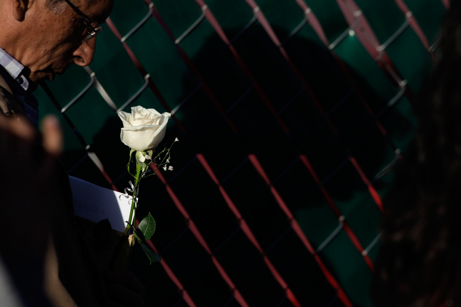 Feb. 26, 2012. A man holds a rose as relatives of victims of a casino arson attack gather outside the casino in Monterrey, Mexico.