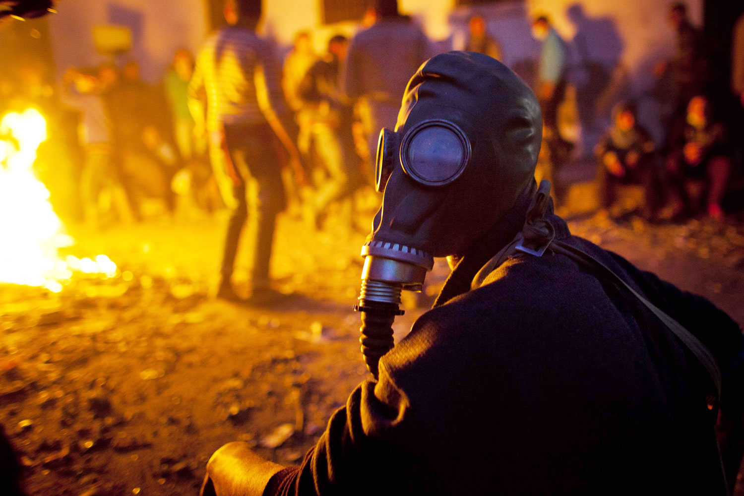 February 3, 2012. A protester wearing a gas mask sits close to a fire as protests near to Egypt's Interior Ministry continued for a second consecutive day in Cairo.