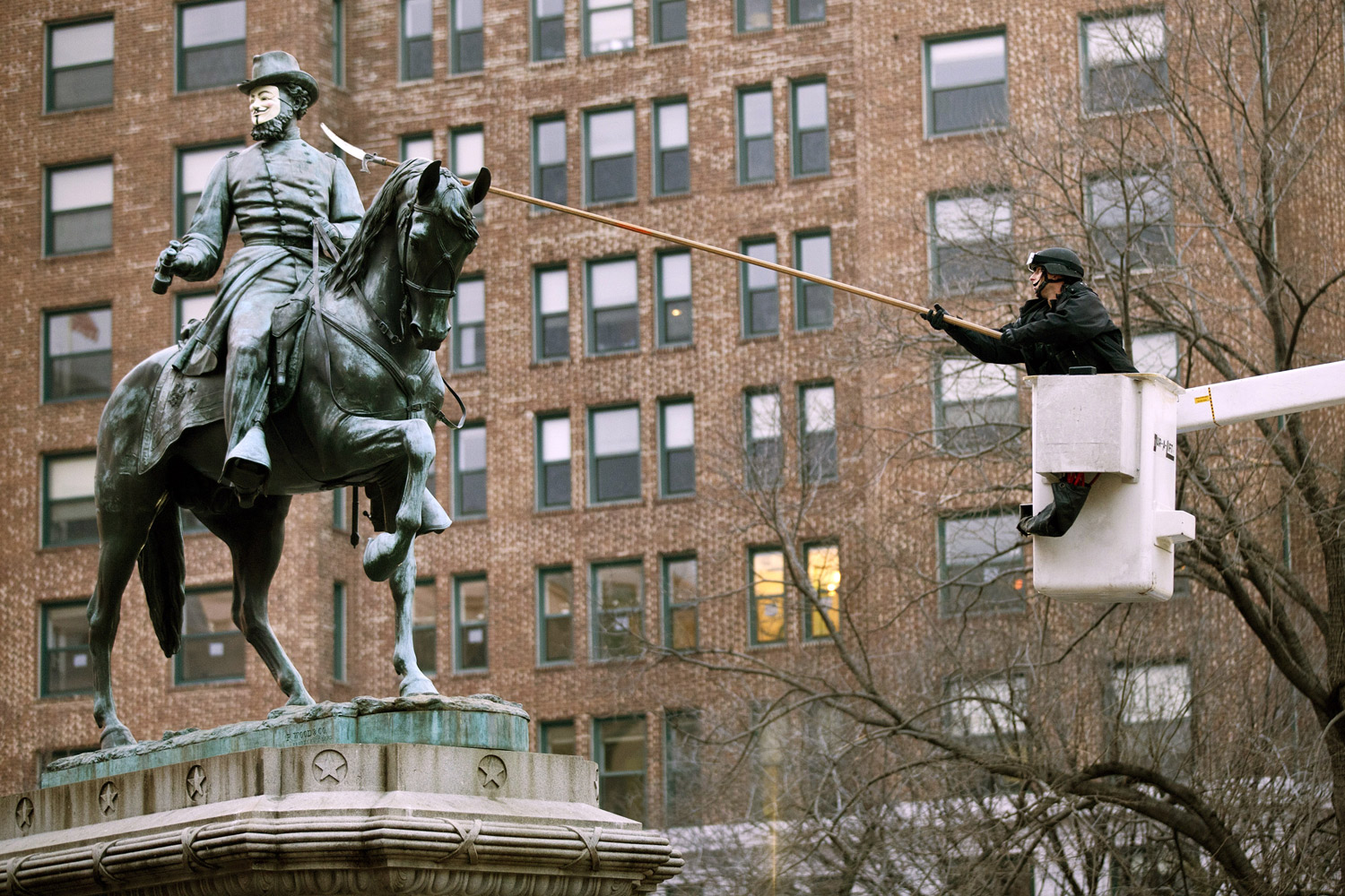 February 4, 2011. A US Park Police officer uses a limb saw to remove a mask of Guy Fawkes from a statue of James McPherson in McPherson Square in Washington, D.C.