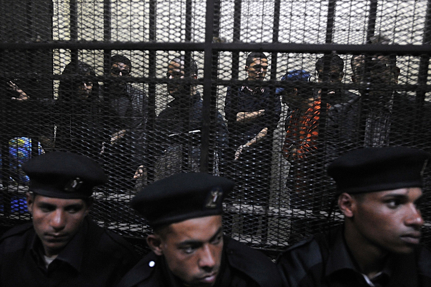 Feb. 26, 2012. Defendants accused of working for unlicensed non-governmental organizations and receiving illegal foreign funds stand in a cage during the opening of their trial in Cairo.