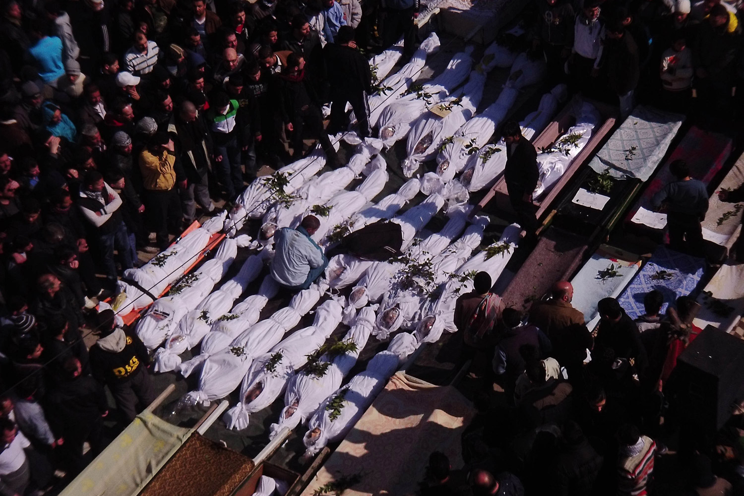 February 7, 2012. Syrian mourners gather around the bodies of people allegedly killed by Syrian government forces during a funeral procession in Maarat al-Noman, Idlib province, Syria.