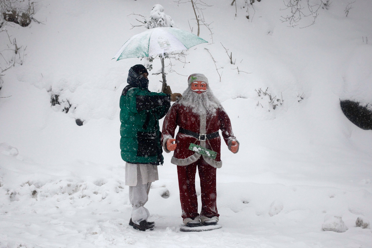 February 4, 2012. Raheem Khan, 35, removes snow from a statue of Santa Claus as he waits for customers during snowfall in the hill-resort town of Murree north east of Islamabad.
