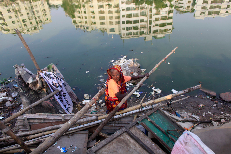 February 6, 2012. A slum dweller retrieves her belongings after a slum was demolished by the police in Dhaka, Bangladesh.