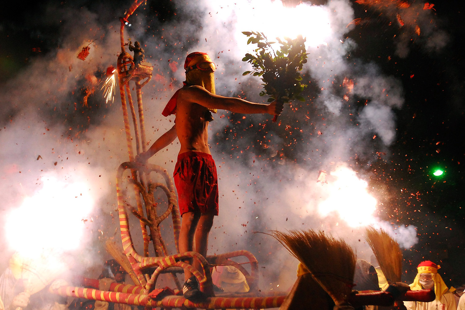February 6, 2012. Worshippers throw firecrackers at a shirtless man acting as Master Handan during the Handan ritual as part of the Chinese Lantern Festival celebrations or  Yuan Hsiao Jie  in Taitung, eastern Taiwan.