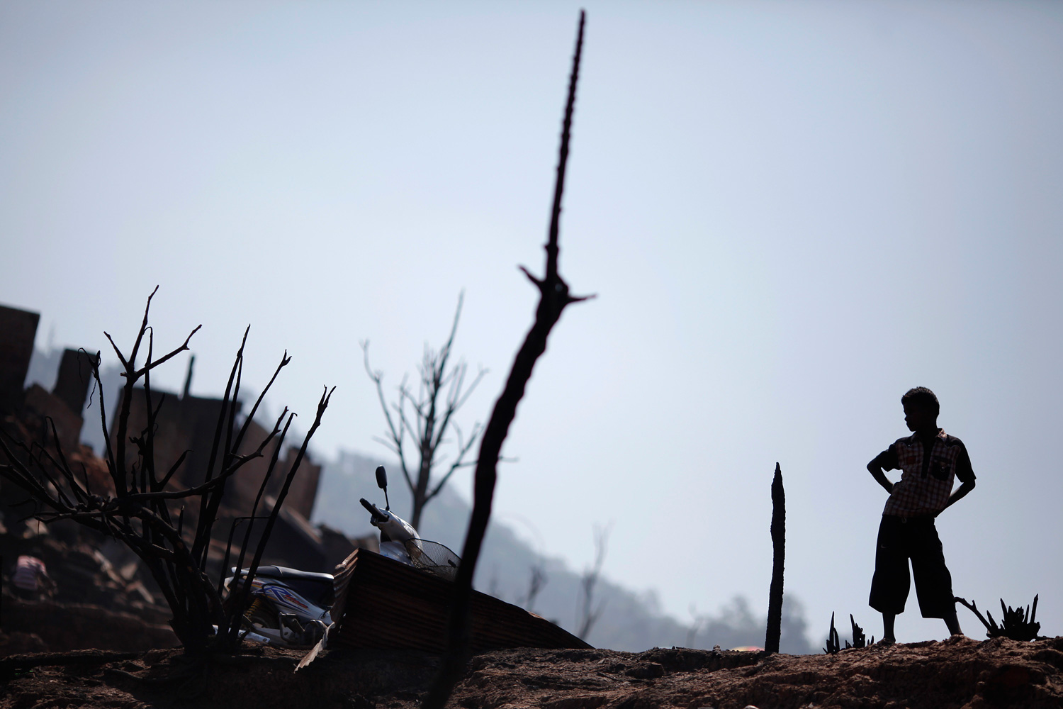 Feb. 24, 2012. A refugee boy from Myanmar stands in ruins of the Um-Piam refugee camp after a fire engulfed part of it near Mae Sot, Thailand.