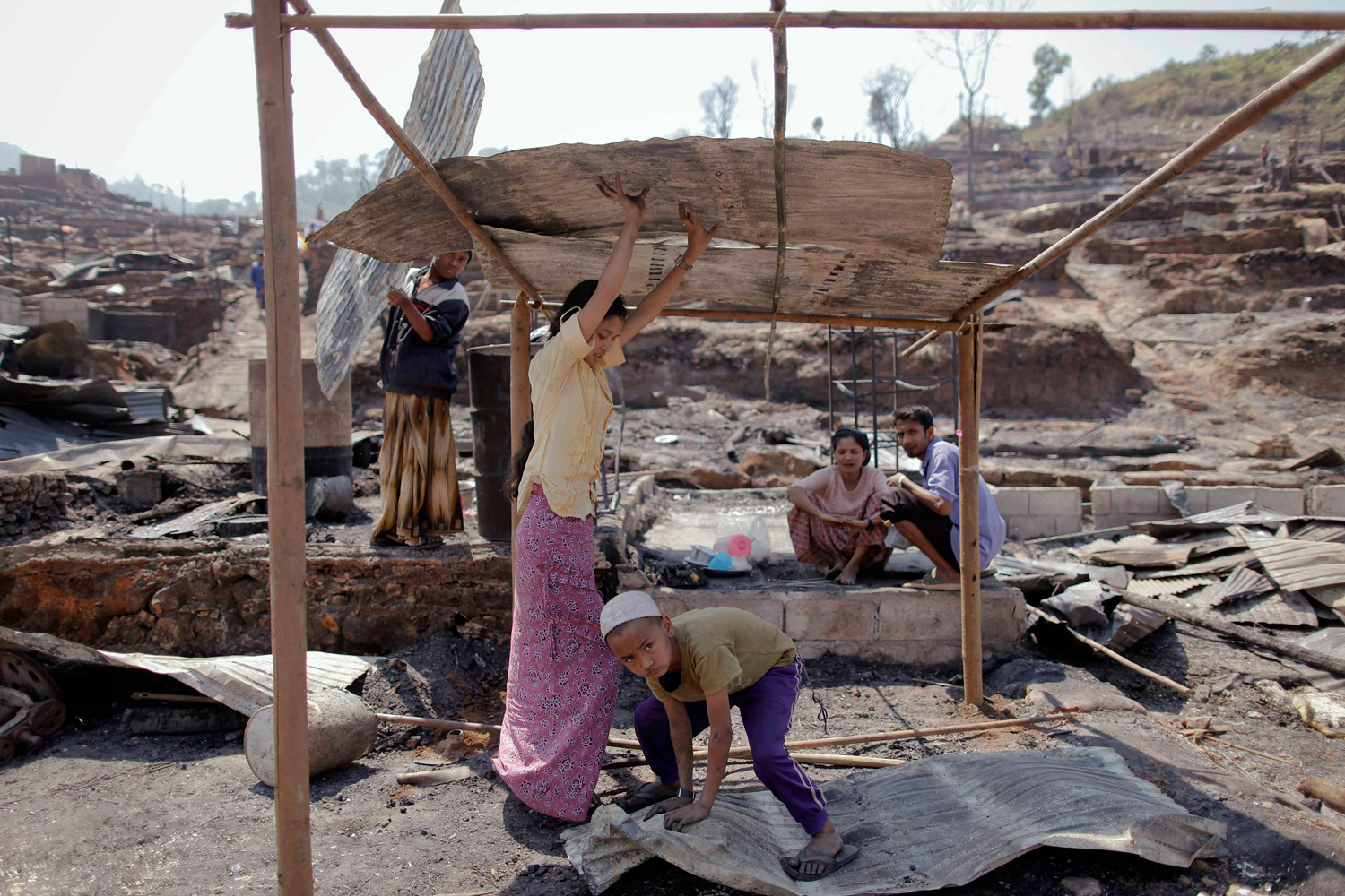Feb. 24, 2012. Refugees make a temporary shelter at the ruins of their burnt home at the Um-Piam refugee camp near Mae Sot, Thailand.