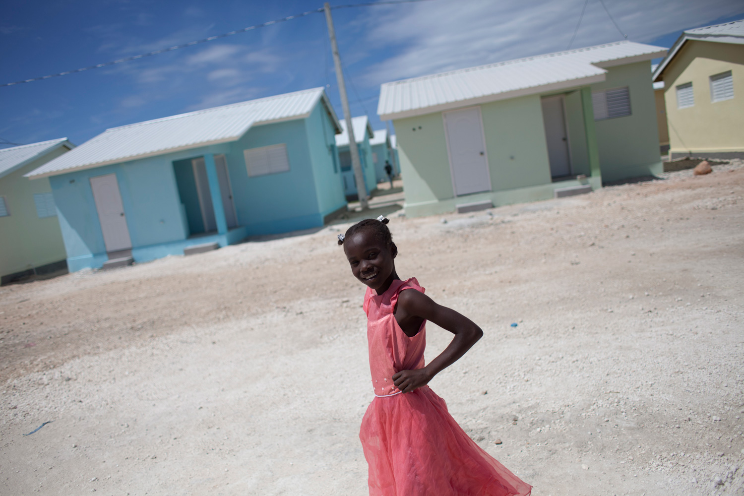 Feb. 27, 2012. A girl poses in front of the newly built houses in Zoranje, City of Soleil, in Port au Prince, Haiti.