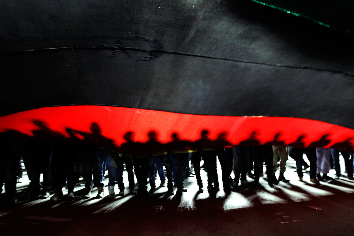 Feb. 25, 2012. People hold a giant Libyan flag during a march to Martyrs Square in Tripoli.