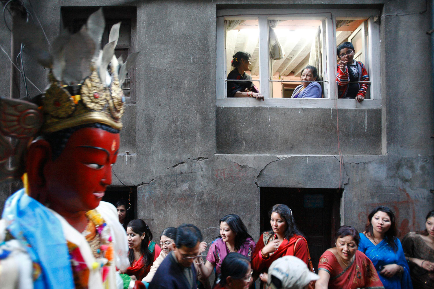 Feb. 25, 2012. Nepalese people watch from the window of their house as a statue of Buddha is brought in at Patan during the Samyak festival in Kathmandu.