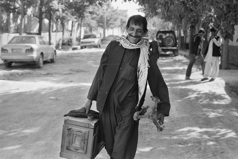 Qalam Nabi walking with his camera.