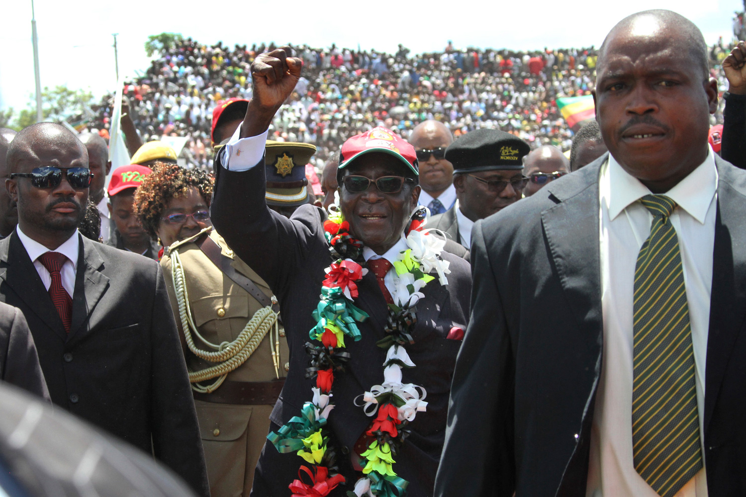 Feb. 25, 2012. Zimbabwean President Robert Mugabe, center, greets the crowd as he arrives for his 88th birthday celebrations in Mutare, Zimbabwe.