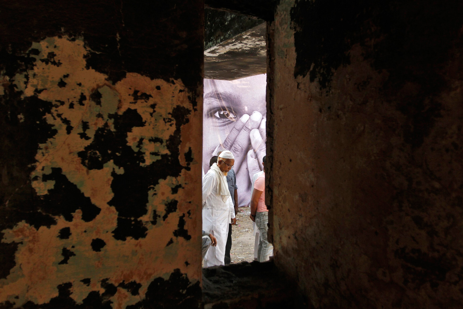 Feb. 27, 2012. A survivor stands outside his house that was burnt and damaged in the Godhra riots during the commemoration of its 10th anniversary, in the western Indian city of Ahmedabad.