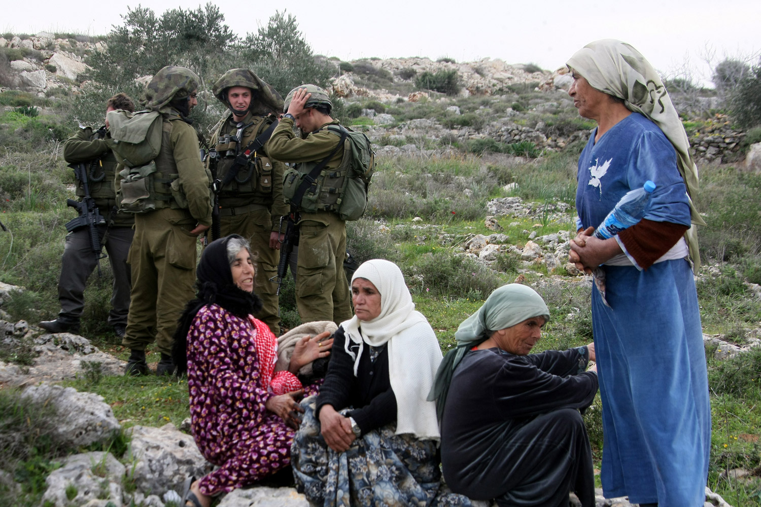 February 6, 2012. Israeli soldiers stand guard as Palestinian women gather while Jewish settlers from the settlement of Kedumim plough in the West Bank.