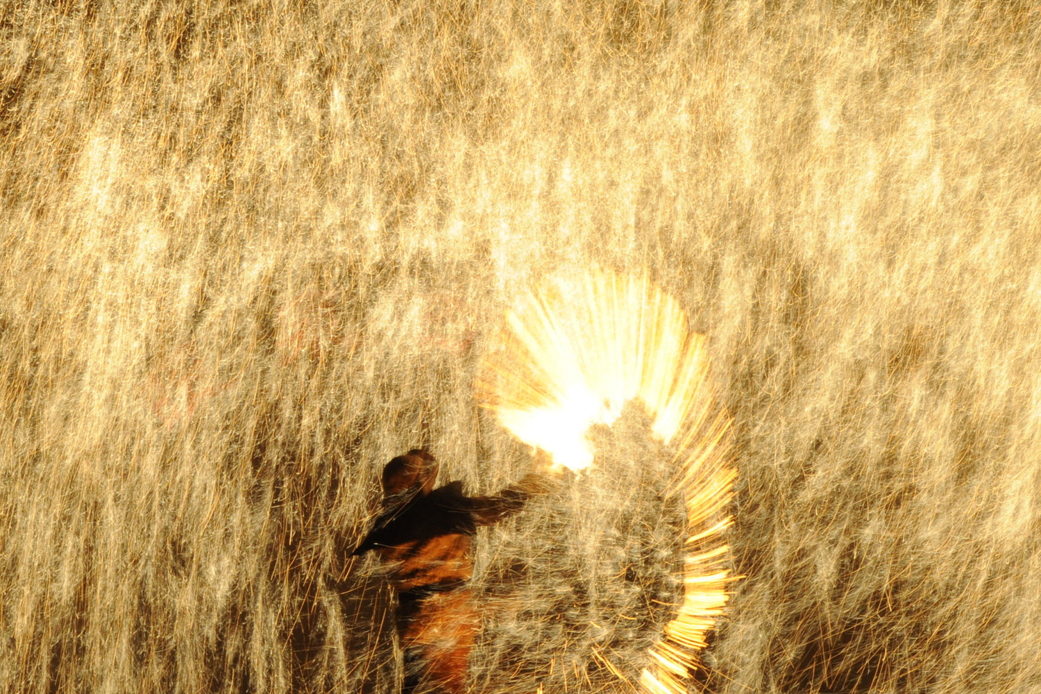 February 6, 2012. A blacksmith throws molten metal against a cold wall to create sparks, as he and others celebrate the Lantern Festival which traditionally marks the end of the Lunar New Year celebrations, in Nuanquan, China.