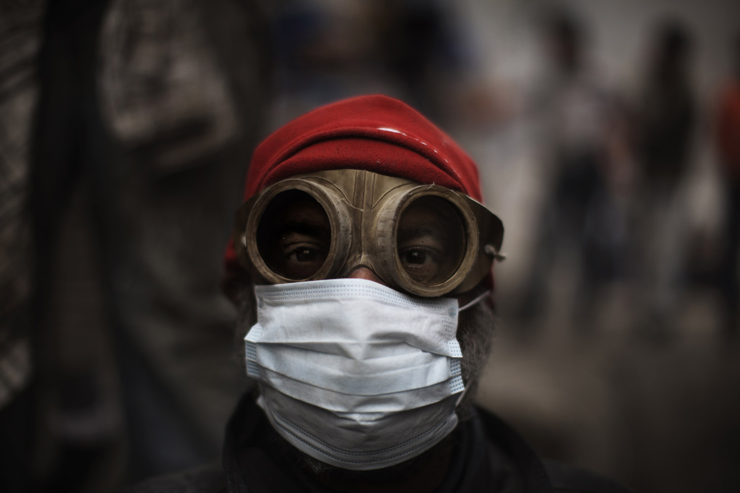 February 6, 2012. An Egyptian demonstrator uses goggles and a protective mask against tear gas fired by riot police during confrontations outside Cairo's security headquarters.
