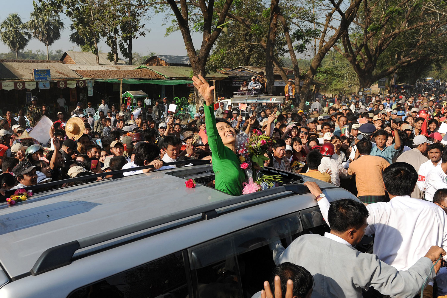 February 7, 2012. Myanmar opposition leader Aung San Suu Kyi (C) waves as she crosses a crowd of supporters while arriving for a political rally as part of her electoral campaign at a stadium in Pathein, Myanmar.